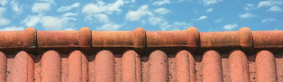 blauwe lichtbewolkte lucht en dak met rode dakpannen
